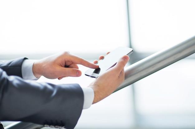 Молодой бизнесмен, работающий с цифровым планшетным компьютером современных устройств и мобильным телефоном