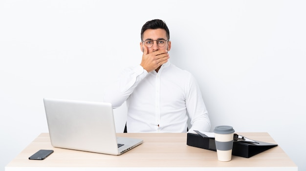 Young businessman in a workplace covering mouth with hands