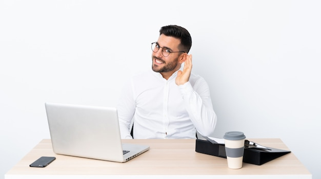 Young businessman in a workplace listening to something by putting hand on the ear