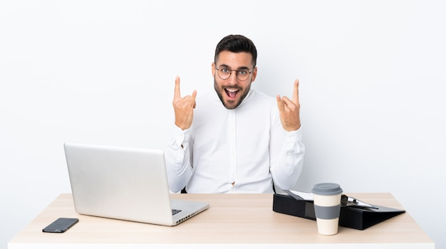 Young businessman in a workplace making rock gesture