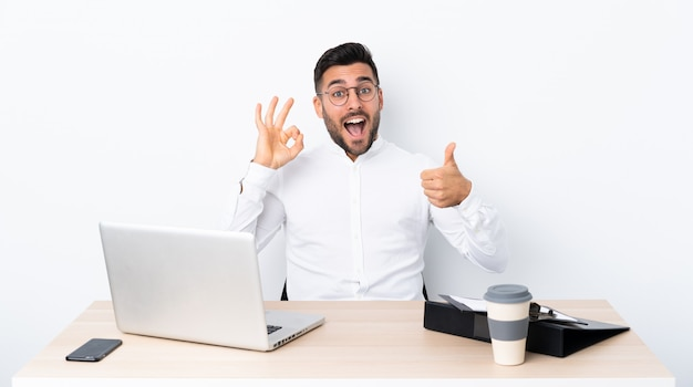Young businessman in a workplace showing ok sign and thumb up gesture