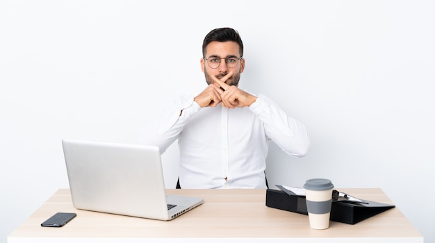 Young businessman in a workplace showing a sign of silence gesture
