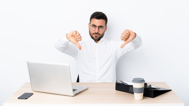 Young businessman in a workplace showing thumb down