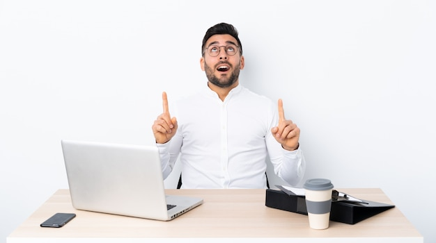 Young businessman in a workplace surprised and pointing up