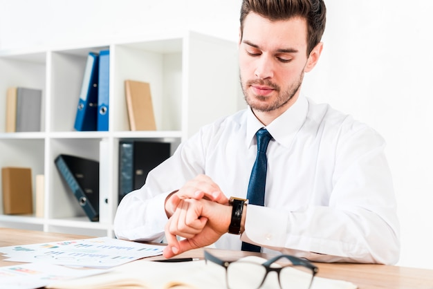 Young businessman at workplace watching the time on wrist watch