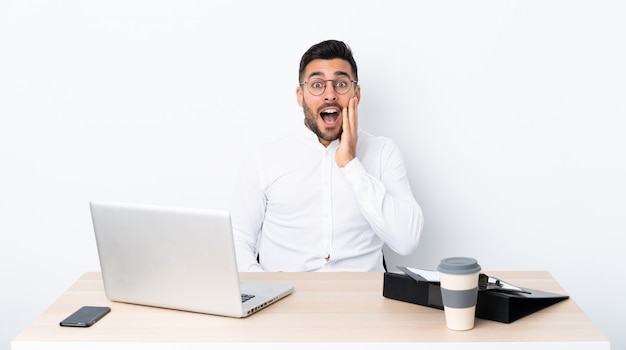 Young businessman in a workplace with surprise and shocked facial expression