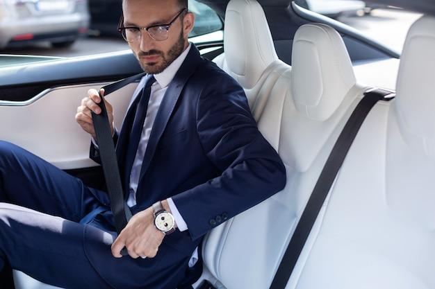 Молодой бизнесмен. молодой бизнесмен в темном костюме, пристегивая ремень безопасности, сидя на заднем сиденье