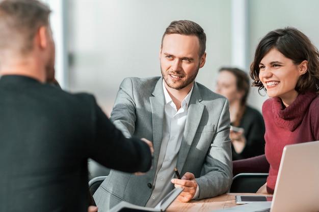 若いビジネスマンは握手で取引を確認します