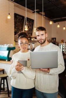 Молодые бизнесмены. пара молодых преуспевающих бизнесменов, стоящих в собственной кофейне и работающих