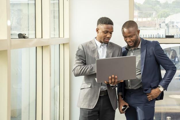 Giovani uomini d'affari in piedi insieme con in mano un laptop, discutendo di affari