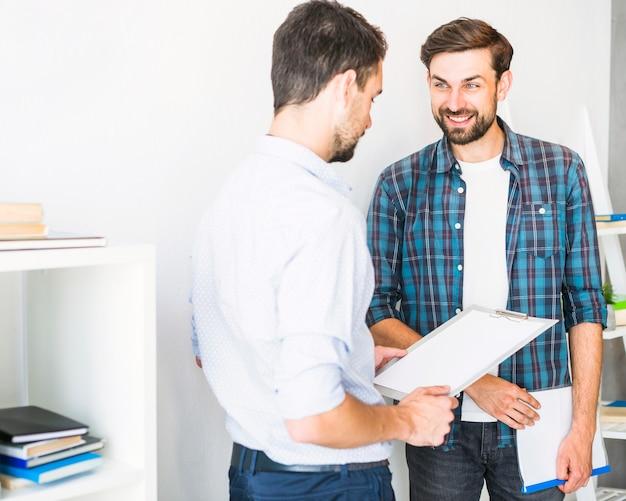 オフィスに立っているフォルダーとクリップボードを持つ若いビジネスマン
