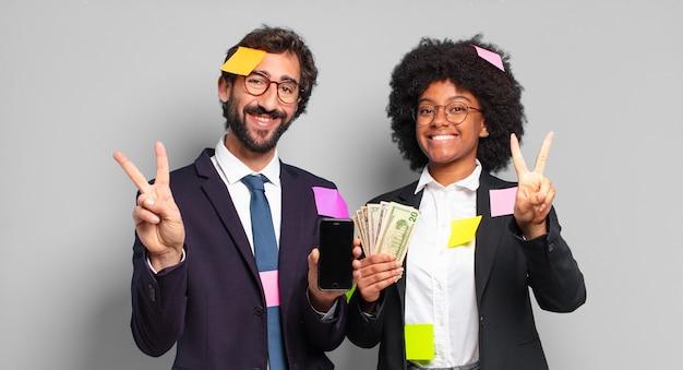 Молодые бизнесмены улыбаются и выглядят счастливыми, беззаботными и позитивными, показывая победу или мир одной рукой. юмористическая бизнес-концепция