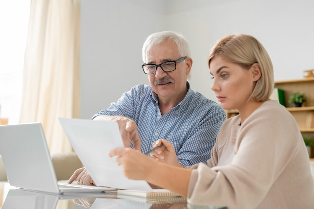 젊은 사업가 사무실에서 작업 회의에서 계약 또는 재정 서류를 논의하는 그녀의 수석 남성 동료
