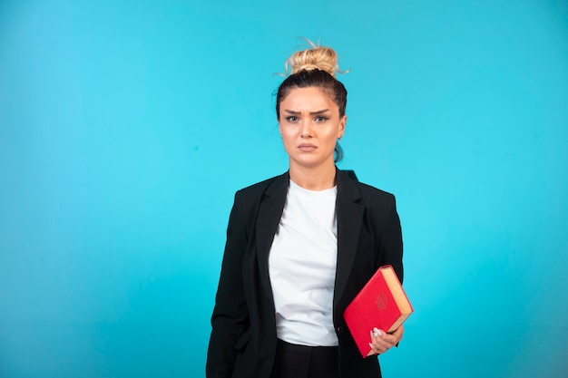 Young businesswoman in black blazer holding a book and looks depressed.