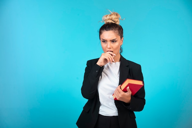Giovane donna di affari in giacca sportiva nera che tiene un libro e pensare