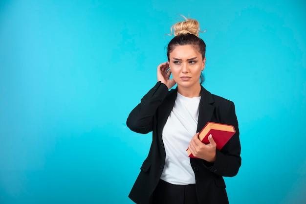 Giovane donna di affari in giacca sportiva nera che tiene un libro e che cerca di ricordare qualcosa.