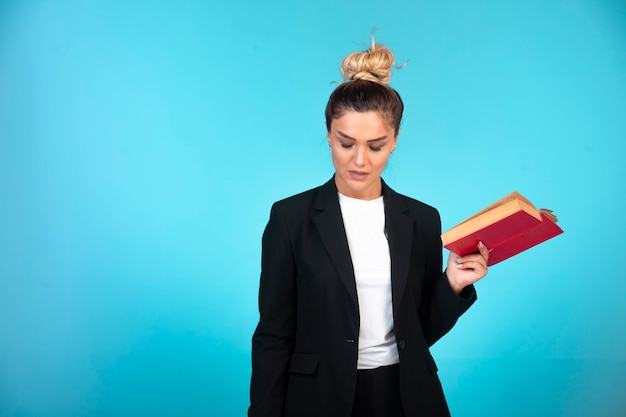 Young businesswoman in black blazer holding a taskbook and checking the meetings