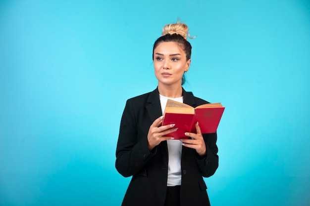 Young businesswoman in black blazer holding a taskbook and thinking.