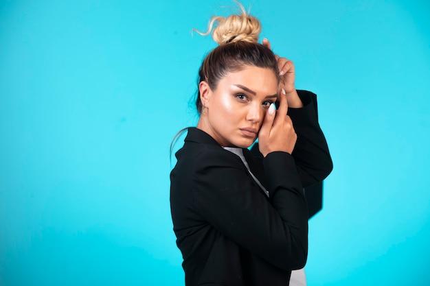 Young businesswoman in black blazer, profile view.
