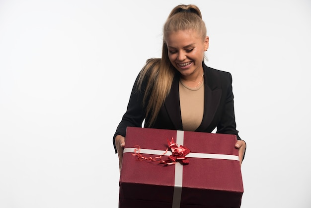 Young businesswoman in black suit holding a big gift box and smiling.
