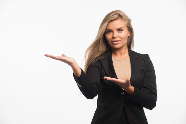Young businesswoman in black suit introducing something.