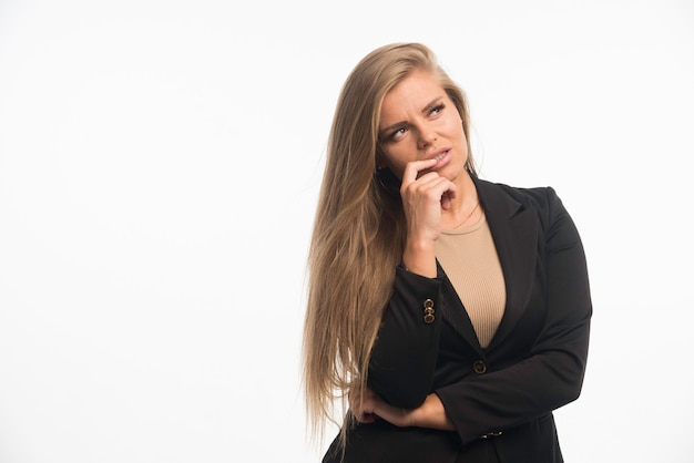 Giovane donna di affari in vestito nero che osserva in su e che pensa.