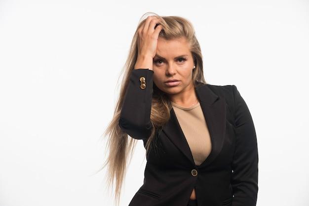 La giovane donna di affari in vestito nero sembra attraente e seducente.