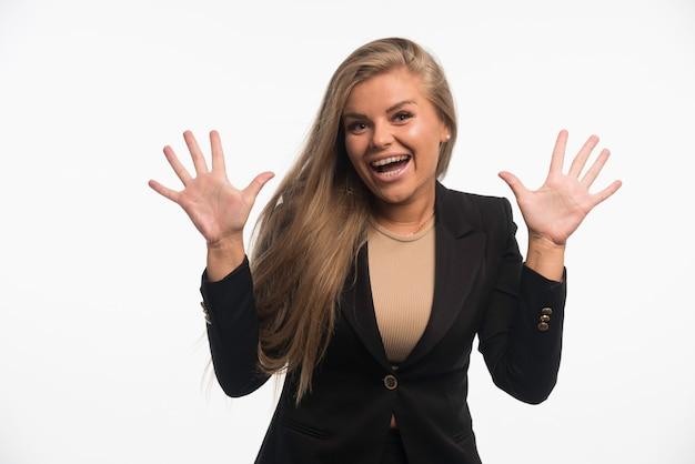 La giovane donna di affari in vestito nero sembra allegra.