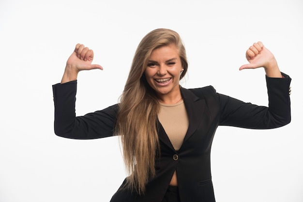 Young businesswoman in black suit looks confident and pointing herself while smiling