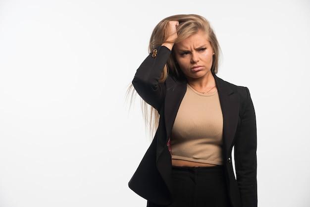 La giovane donna di affari in vestito nero sembra confusa.