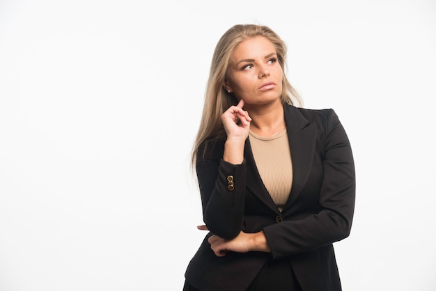 Young businesswoman in black suit looks focused.