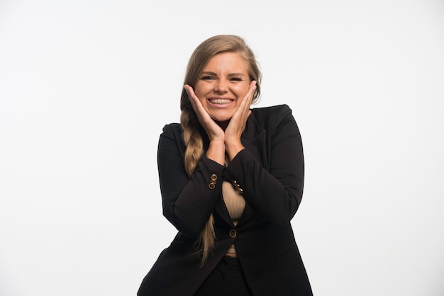 Young businesswoman in black suit looks happy and cheerful.