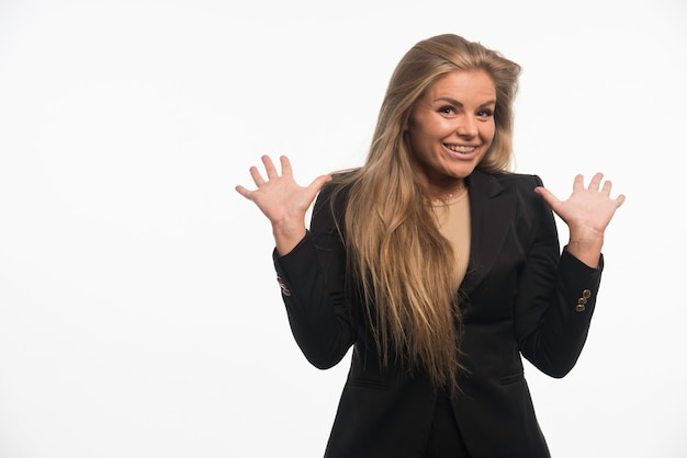 Young businesswoman in black suit opens hand and smiling.
