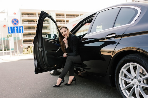 Young businesswoman in black wear with a expensive car