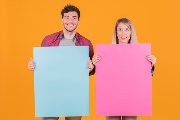 Young businesswoman and businessman holding blue and pink placard against an orange background