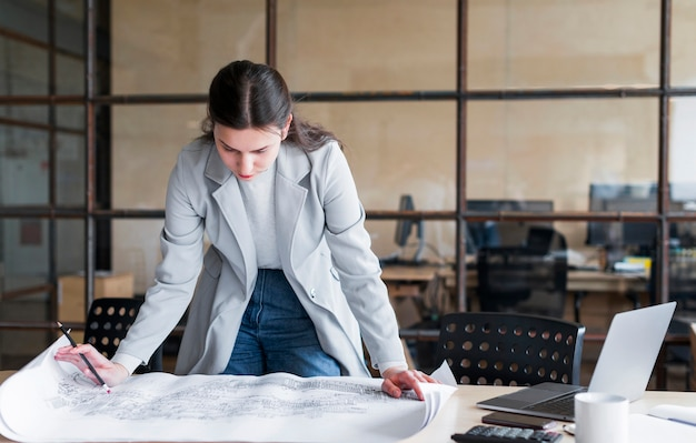 Young businesswoman checking blue print layout