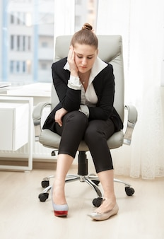 Young businesswoman choosing between comfortable and beautiful shoes