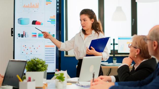 비즈니스 프레젠테이션을 하는 젊은 여성 사업가 코치 리더 회의 연사는 사무실 회의실 세미나 회의에서 디지털 보드 교육 다양한 팀 그룹을 가리키는 프로젝트 전략을 설명합니다.