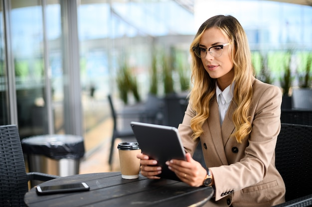 Young businesswoman on a coffee break. using tablet computer.