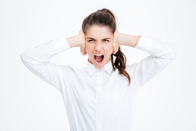 Young businesswoman covering her ears and shouting over white wall
