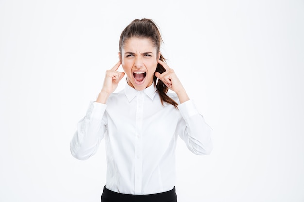 Young businesswoman covering her ears with hands and shouting over white wall