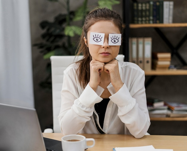 Young businesswoman covering her eyes with drawn eyes on paper