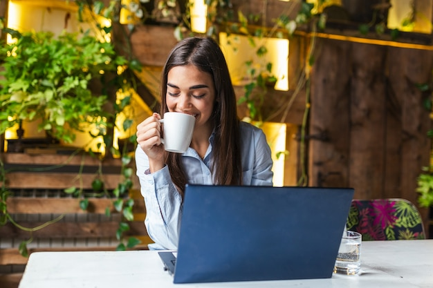 Young businesswoman drinking coffee and using laptop in cafe