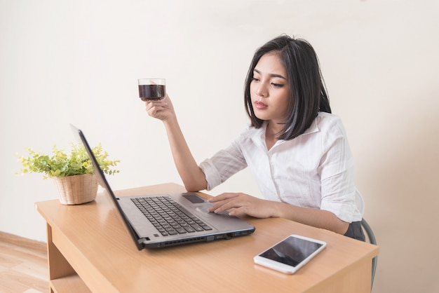 Young businesswoman drinking coffee while working with laptop at the desk.