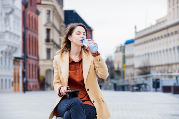 Молодая коммерсантка есть салат и питьевую воду