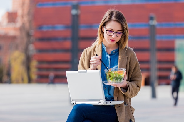 Young businesswoman eating salad and working with computer at urban outdoor