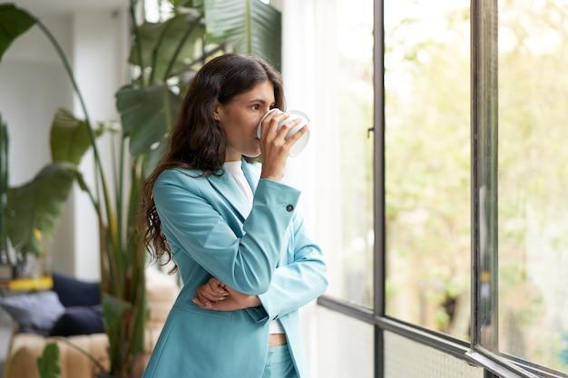 Молодой предприниматель, наслаждаясь утренним кофе или чаем, глядя в окно, красивая латинская женщина ...