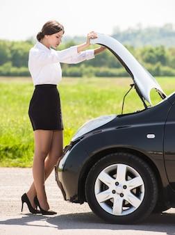 Young businesswoman examining broken down car.
