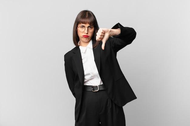 Молодая деловая женщина чувствует себя сердитой, сердитой, раздраженной, разочарованной или недовольной, показывая большие пальцы вниз с серьезным взглядом