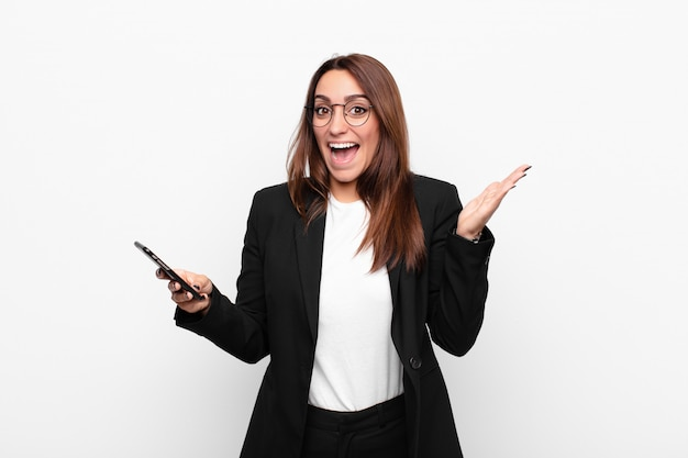 Young businesswoman feeling happy, excited, surprised or shocked, smiling and astonished at something unbelievable and holding a mobile telephone